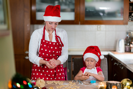 pastry cutters: Mother and daughter are preparing Gingerbread Cookie for Christmas