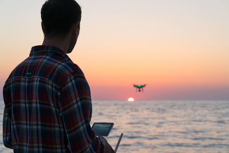 man launches a drone on the beach