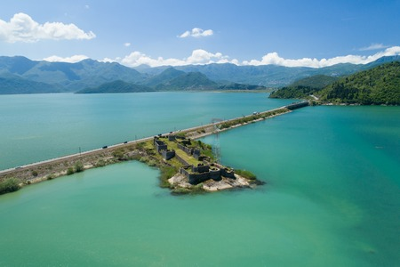 Aerial view of Skadar lake, dam and island with old medieval fortress Lesendro, Montenegro