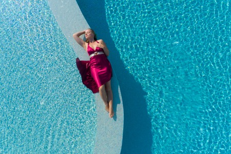Young blonde woman in red dress lying in the swimming pool