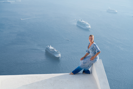 Happy woman in white and blue dress enjoying her holidays on Santorini, Greece. View on Caldera and Aegean sea from Imerovigli. 免版税图像
