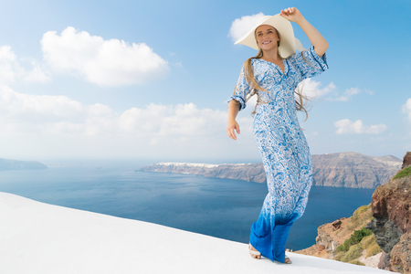 young woman in a white and blue dress enjoys a walk around Santorini 版權商用圖片