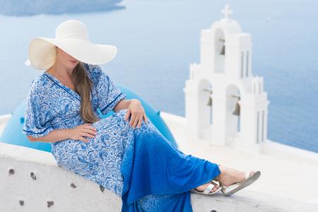 young woman in a white and blue dress enjoys a walk around Santorini Banco de Imagens