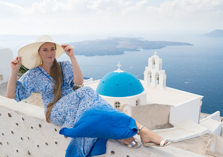 young woman in a white and blue dress enjoys a walk around Santorini Banque d'images