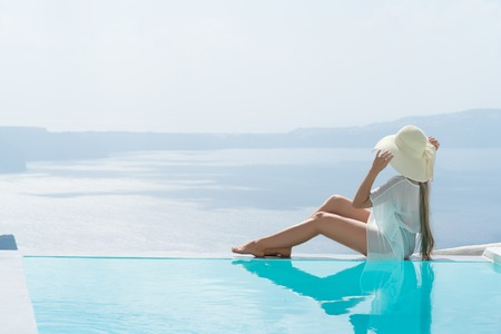 young woman enjoying a magnificent view of Santorini near the pool. 免版税图像