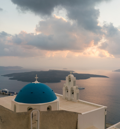 sunset over aegean sea with view to Virgin Mary Catholic Church Three Bells of Fira, Santorini.