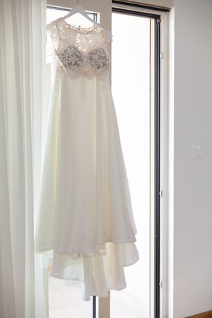 wedding dress hanging on a hanger against the window