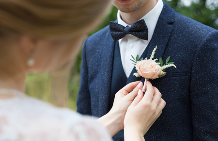 the bride attaches the groom a buttonhole on the lapel of his jacket Stock Photo