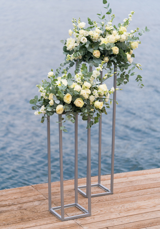 modern stands with flowers on the background of the sea for the wedding ceremony, close up