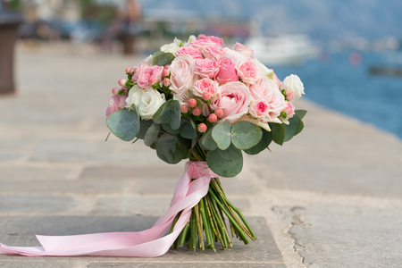 pink-white wedding bouquet stands on a pier near the sea, close up 版權商用圖片