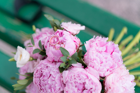 gold wedding rings lie on a bouquet of peonies Archivio Fotografico - 115539536