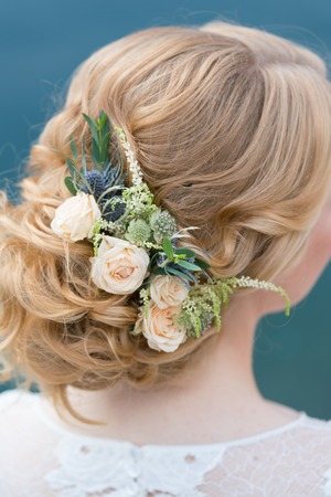 Bridal hairstyle with fresh flowers back view, close up
