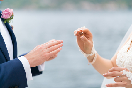 bride puts a ring on the grooms finger, close up