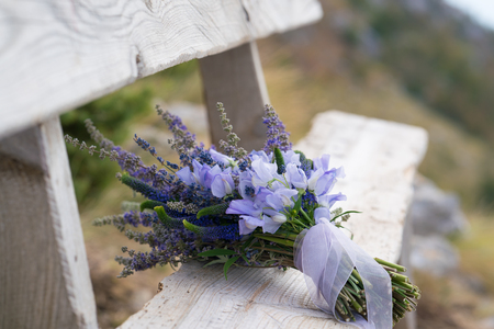 elegant wedding bouquet of purple flowers and herbs lies on the bench