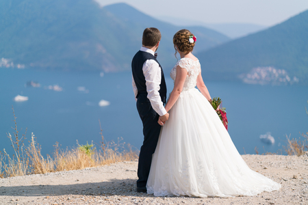 the newlyweds stand on a dais and holding hands look at the sea