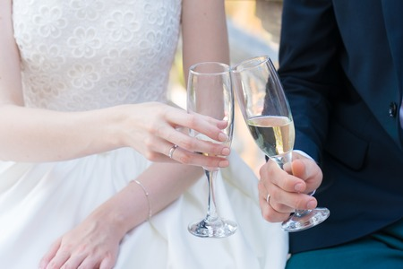 newlyweds are holding champagne glasses and clink glasses