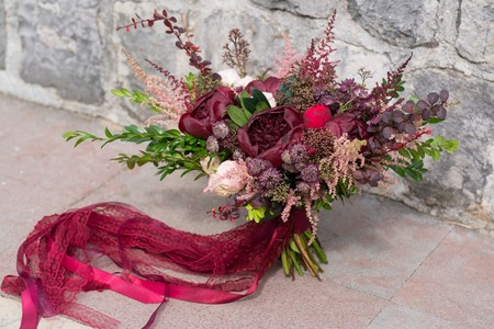 dark red wedding bouquet stands on stone wall background