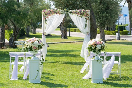 rectangular wooden wedding arch decorated with flowers and fabric for a wedding ceremony on the meadow 스톡 콘텐츠