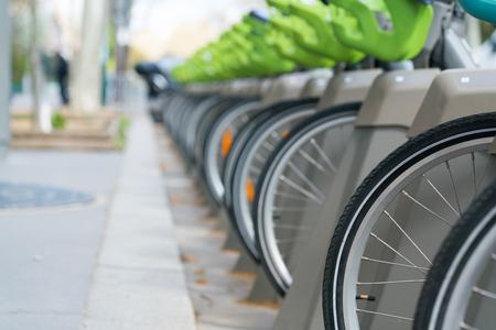 Fiets te huur, aantal wielen staat op parkeerplaats. Stockfoto