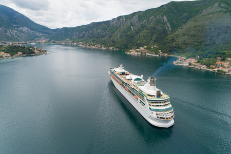 Aerial view of luxury medium cruise ship sailing to port through the bay, Montenegro Stockfoto