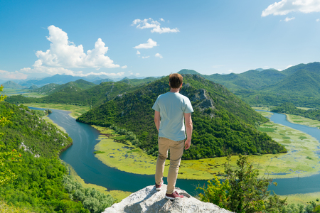 guy posing on the background of a curved river and mountains in Montenegro 版權商用圖片