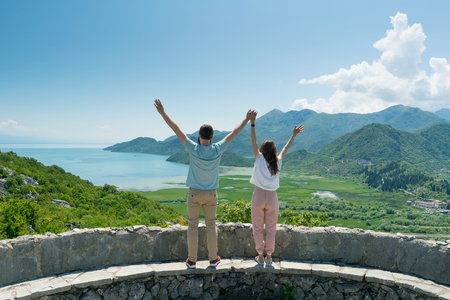 couple on a viewing platform enjoying the view of the lake and mountains on a sunny day, Montenegro 版權商用圖片