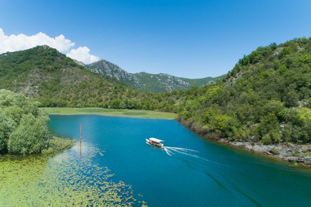 motor boat floats on a Crnojevica river framed by water lilies, Montenegro Stockfoto