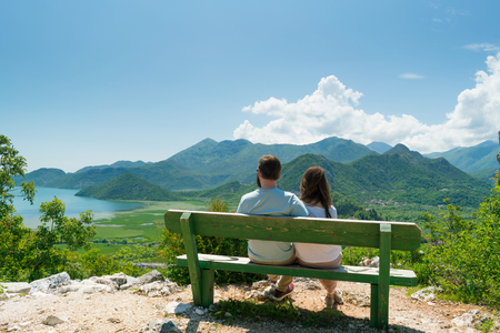 couple sits on a bench and admires the view of the lake and hills on a sunny day 版權商用圖片