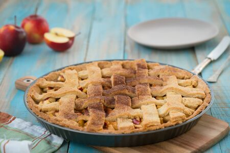 Home-baked lattice apple pie, in a baking dish, ready to serve.