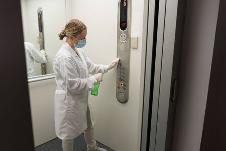 Woman using wet wipe and alcohol sanitizer spray to clean an elevator push button control panel. Disinfection, cleanliness and health care, Anti Coronavirus COVID-19