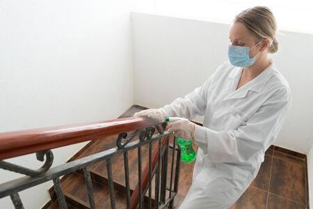 Woman using wet wipe and alcohol sanitizer spray disinfects railing. Disinfection, cleanliness and health care, Anti Coronavirus COVID-19