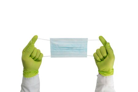 Hands in rubber gloves hold a protective medical mask. Surgical mask isolated on a white background.