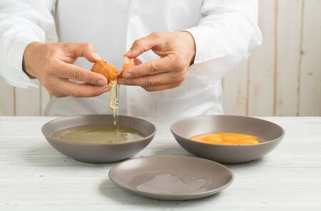 open one organic egg in the hands of the chef to separate egg yolk