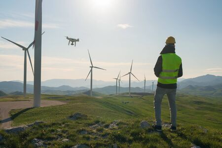 Technician Engineer in Wind Turbine Power Generator Station launches a drone for visual control of generators Stok Fotoğraf