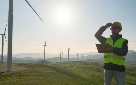 Technician Engineer in Wind Turbine Power Generator Station standing with a tablet in his hands