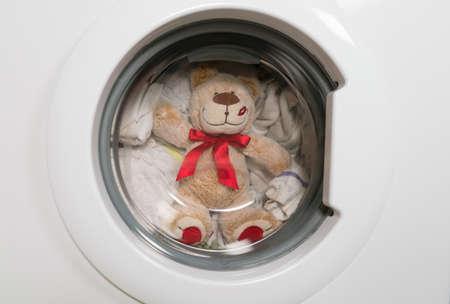 Teddy bear washes in the washing machine.