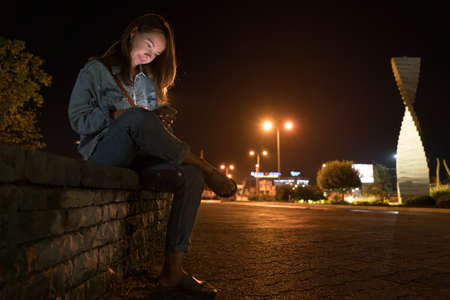 Young woman using mobile phone on street at night