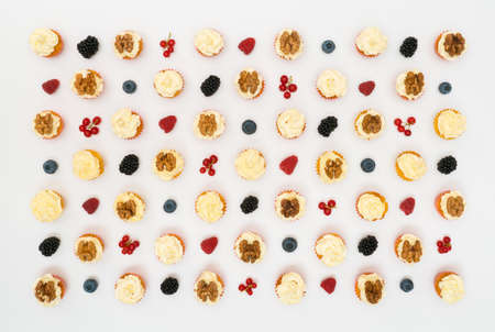 cupcakes and berries neatly laid out on a white background