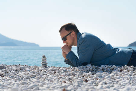 a man in a jacket lies on the beach and looks at the zen pyramid