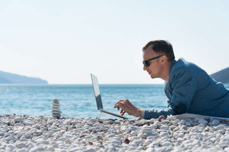 freelancer businessman working remotely on laptop at the beach near the zen pyramid