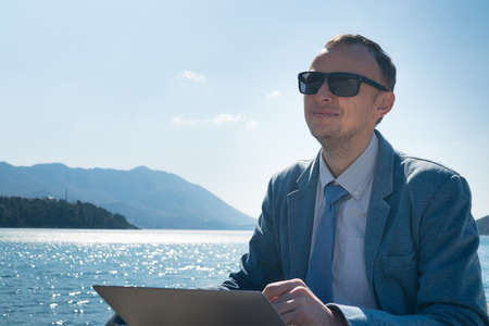 freelancer businessman working remotely on laptop while sitting on the pier