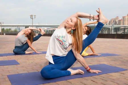 Beautiful woman doing Vriksasana pose on yoga class