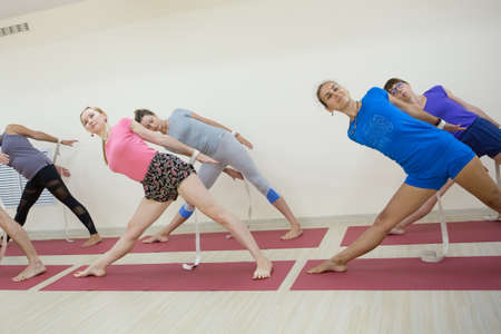 Group of positivel people practicing yoga in gym Teamwork, good mood and healthy lifestyle concept