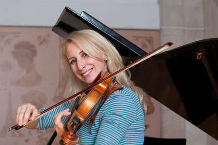 Young positive blonde playing violin Portrait