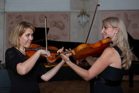 Two beautiful female violinists playing violin Close-up portrait