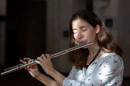 A beautiful woman posing while playing on a flute Genre portrait of young beautiful girlr Close-up Stock Photo