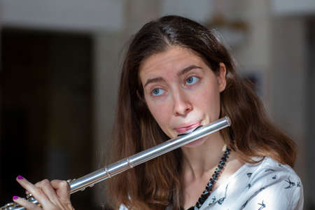 A beautiful woman posing while playing on a flute Genre portrait of young beautiful girlr Close-up 写真素材