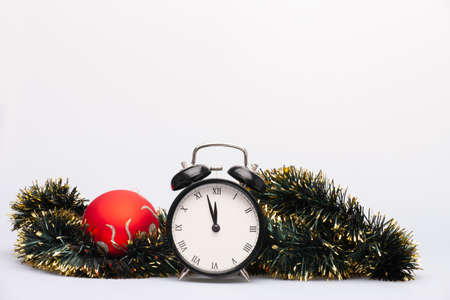 An alarm clock, red bauble and green tinsel for christmas decoration