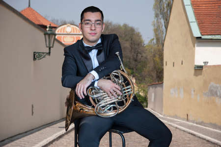 French horn player. Hornist playing brass orchestra music Portrait on the background of the city Close-up Standard-Bild