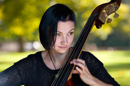 Young positive brunette playing double bass Portrait